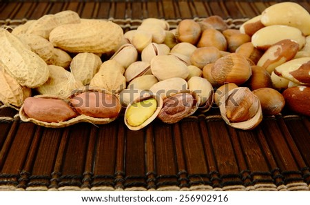 Many nuts like peanuts,walnuts,pistachios and brasil nuts, snacks in group on brown mat - stock photo