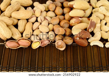 Many nuts like peanuts,walnuts,pistachios,cashew nuts and brasil nuts, snacks in group on brown mat - stock photo