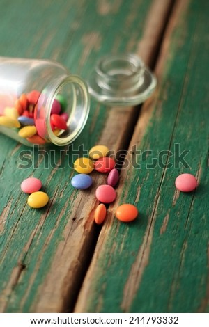 Many of color chocolate smarties placed on worn wooden board with old green color with visible groove between two boards and with glass jar in back - stock photo