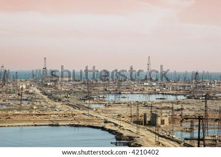 Many oil derricks on the shore near Baku, Azerbaijan - stock photo