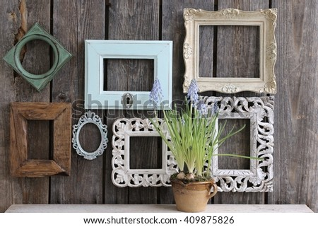 Many old frames of rectangular, square, oval, composition with vintage wooden frames on the wall, fresh  flowers in the very old clay cup - stock photo