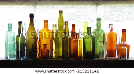 Many old glass bottles on windowsill in daylight.  - stock photo