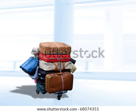 Many old suitcases on a cart at the airport - stock photo