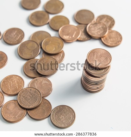 Many one cent euro coins with some on a column isolated on a white background.
