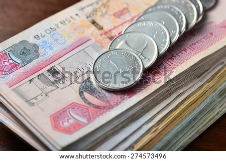 many one dirham coins placed on stack of hundred dirham notes. Close up. - stock photo