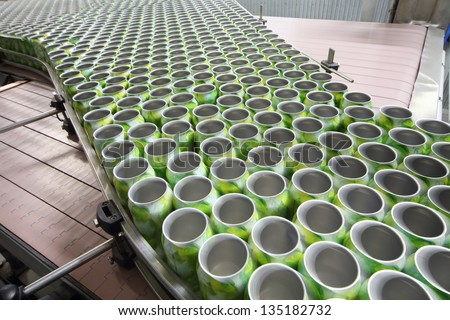 Many open green cans for drinks move on conveyor at large modern factory. - stock photo