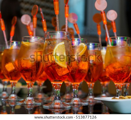 many orange cocktails on night party in dark room