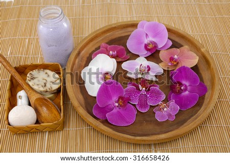 Many orchid in wooden bowl with spa set  on mat