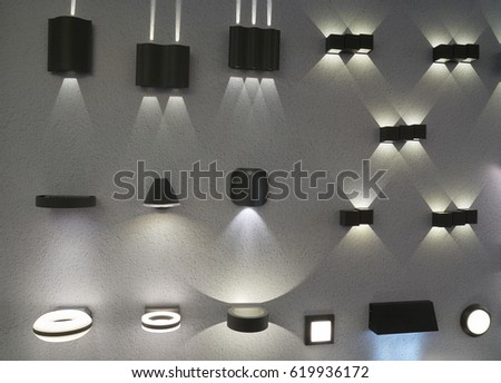 Many outdoor and indoor electric lamps mounted on the wall of the store