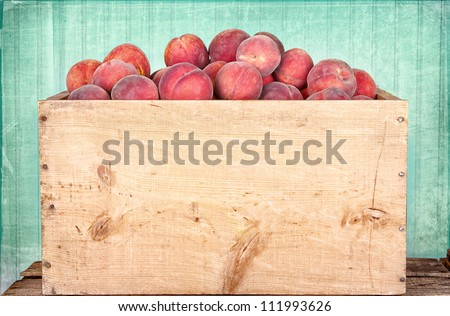 Many peaches in wooden crate with antique panel background - stock photo