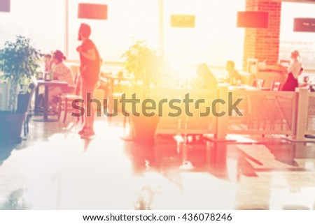 Many people eating in the restaurant. Sun shining through the window. Blurred effect applied. - stock photo