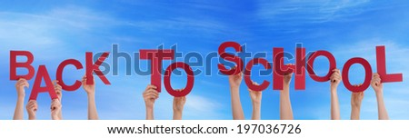 Many People or Children Holding the Words Back To School in the Sky - stock photo