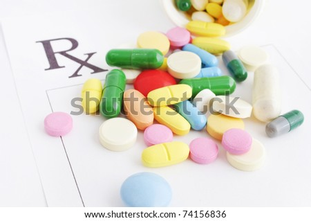 Many pills and capsules falling from an opened box on a prescription form - stock photo
