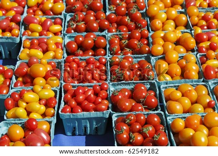 Many pints of small orange and red tomatoes in pint containers for sale at an outdoor market.
