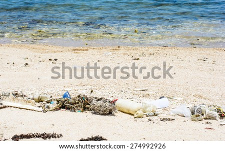 Many plastic and garbage is a pollution on the beach,Focus on garbage and blurry on water - stock photo