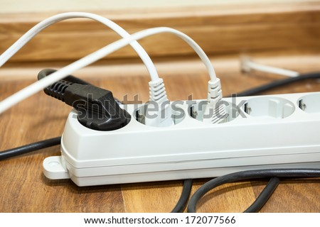 Many plugs plugged into electric power bar on office floor