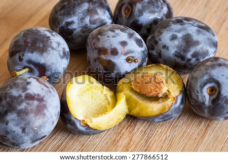 Many plums on wooden table