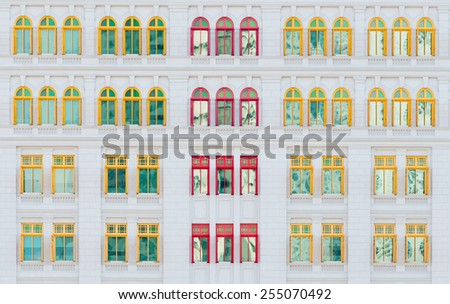 Many red and yellow open windows on light exterior wall of old vintage classical building - stock photo