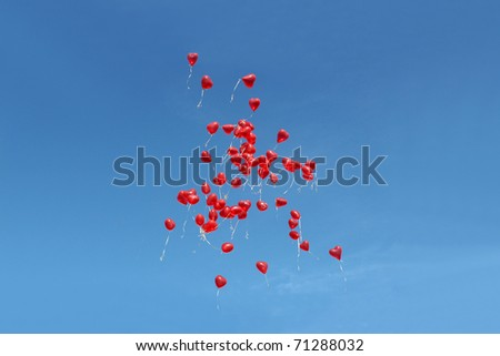 Many red balloons in front of blue sky - stock photo