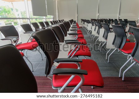 Many red chairs arranged neatly in a training room.