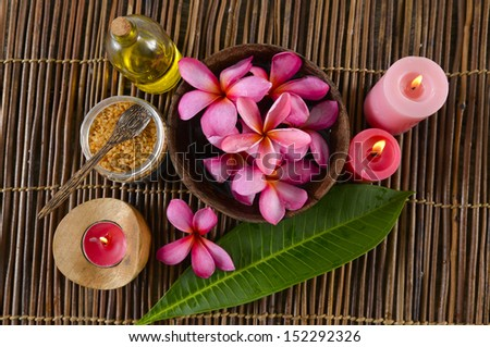 Many red frangipani in bowl ,red candle ,leaf ,candle ,oil on bamboo mat