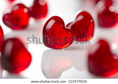Many red glass hearts on white background - stock photo