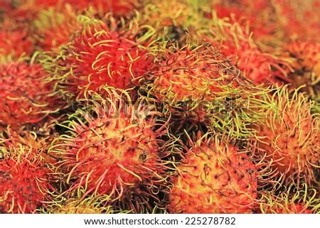 Many red rambutan. The macro. Tropical fruits. - stock photo