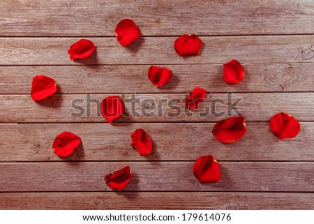 Many red rose petals on a wooden table