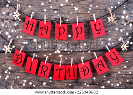 Many Red Tags with Happy Birthday Wishes on a Line Hanging in the Snow in front of a Rustic Wooden Panel - stock photo