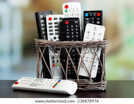 Many remote control devices in basket on bright background - stock photo