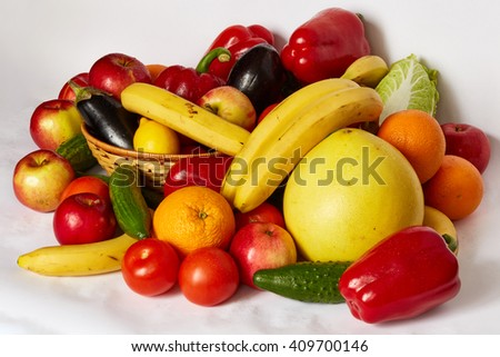 Many ripe fruit and vegetables are spread out on a white background - stock photo