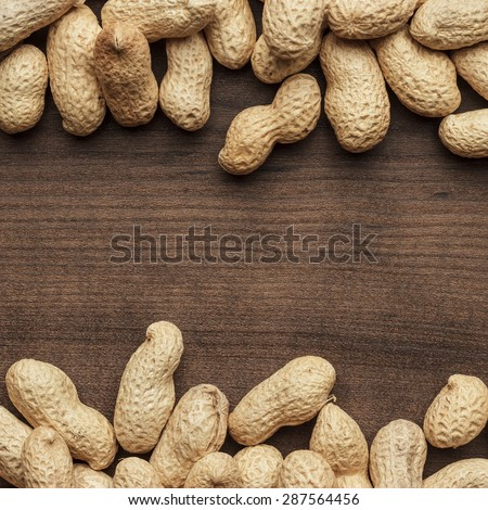 many roasted peanuts on the wooden table background with copy space - stock photo