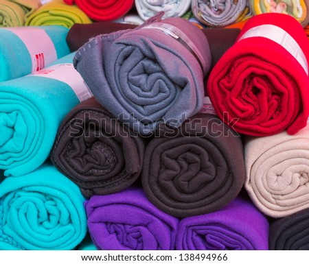 Many rolled colorful fleece blankets
