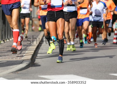 many runners during the marathon in the city street - stock photo