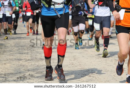 many runners racing on the road while riding in a race - stock photo