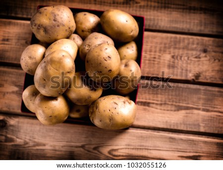many russet potatoes in crate on table