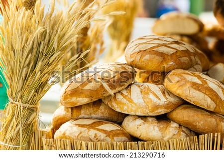 many rustic baked traditional rye bread loaves on a market stall outdoor