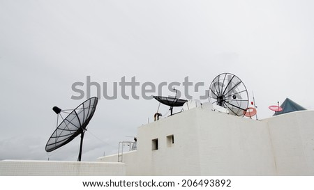 Many satellite dishes on the roof - stock photo