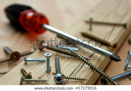 Many scattered screws, detail of screw screwed into a wooden plank, screwdriver in the background - stock photo