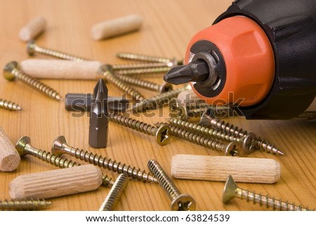 Many screws and a screwdriver on a pine board - stock photo
