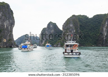 Many ships and tourist at Halong Bay, Vietnam. Unesco World Heritage Site. Most popular place in Vietnam. - stock photo