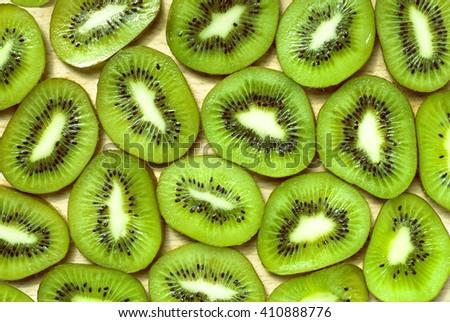 Many slices of kiwi fruit. Green background. Juicy fruit. - stock photo