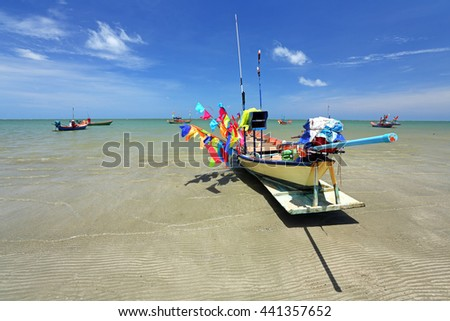 Many small fishing boats and flags of various colors with bright colors after the blue sky background - stock photo