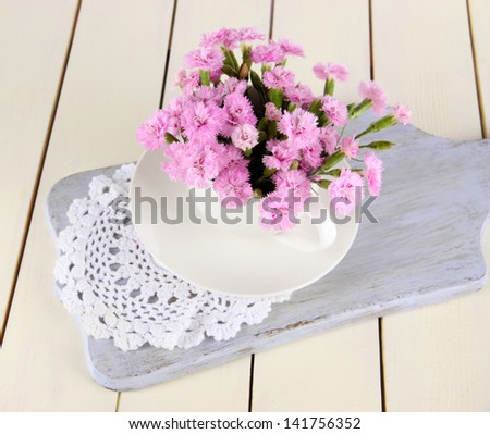 Many small pink cloves in cup on wooden board on beige background