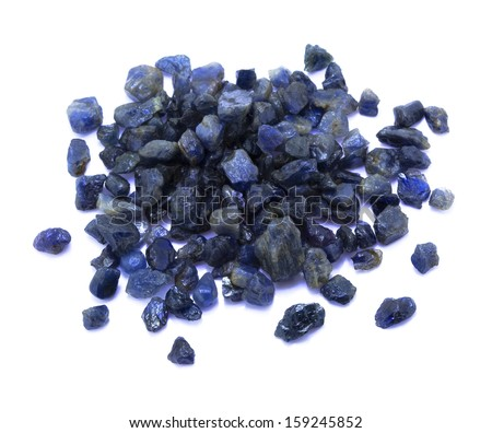 Many small uncut and unpolished dark blue sapphire gems on the white background. - stock photo