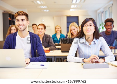 Many smiling students learning in a university class - stock photo