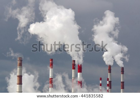 Many smoking chimneys against the sky - stock photo
