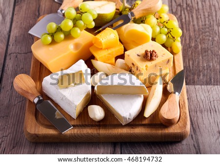 Many sorts of cheese with fruits over wooden board