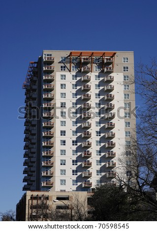Many-storied apartment (condo) building on blue sky background - stock photo