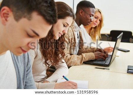 Many students learning with laptop computer in lecture of university - stock photo